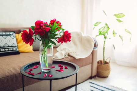 Interior of living room decorated with peonies flowers, plants and carpet. Cozy couch with cushions and table