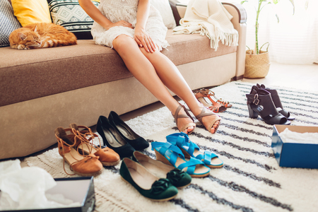 Young woman choosing summer shoes and trying them on at home. Hard choice to make from sandals, heels and flats. Daily decision