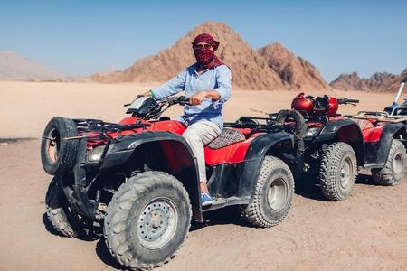 Senior man driving quad bike in Sinai desert. Happy tourist having fun during summer vacationin Egypt