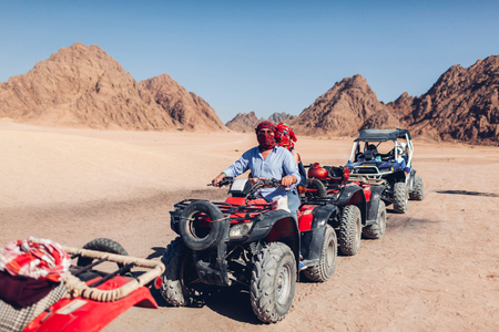 Man and his daughter driving quad bike in Sinai desert. Happy family having fun during summer vacation in Egypt