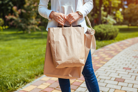 Young woman holding shopping paper bags in summer park and wearing trendy outfit. Purchases Reklamní fotografie