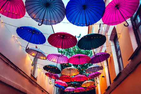 City street decorated with colorful umbrellas and lights. Architecture exterior design in the evening. Night background.