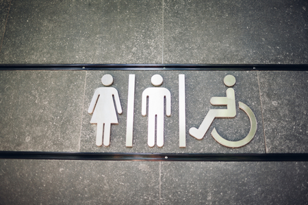 Sign of public toilets WC on city street wall outdoors. For female, male and disabled people.