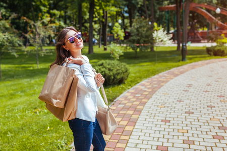 Young happy woman holding shopping paper bags in summer park and wearing trendy outfit. Purchases Reklamní fotografie