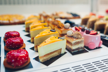 Assortment of different cakes on cafe showcase. Variety of flavours. Chocolate and cream cakes in store with fruits and jelly. Reklamní fotografie