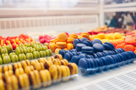 Assortment of colorful macaroons on cafe showcase. Variety of macaron flavours. Sweet almond cakes in store. French biscuits. Reklamní fotografie
