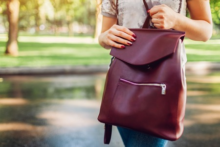 Young woman holding stylish leather backpack outdoors. Spring female clothes and accessories. Fashion