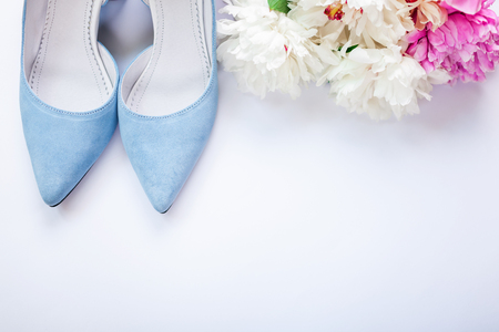 Female blue wedding shoes with bouquet of peonies flowers on white background