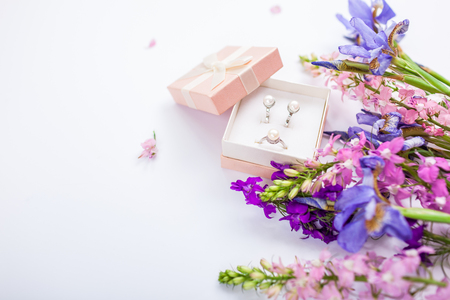 Set of silver ring and earrings with pearls in the gift box with purple irises. Present for holiday with flowers