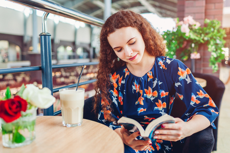 Happy young woman reading book in shopping center while drinking coffee. Relaxing in cafe