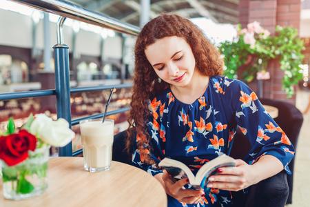 Libro di lettura felice della giovane donna nel centro commerciale mentre beve il caffè. Rilassarsi al caffè