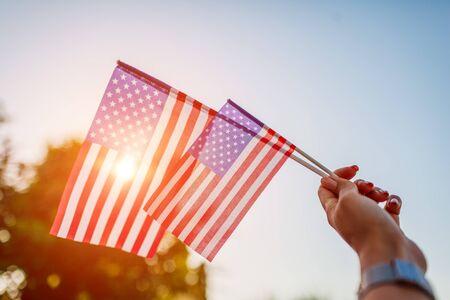 Femme tenant le drapeau des USA contre le ciel bleu. Célébrer le jour de l'indépendance de l'Amérique