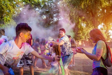 Myrhorod, Ukraine - June 16, 2019: Group of a young people throwing paints on indian Holi festival of colors