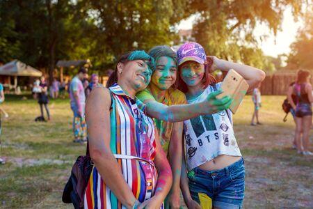 Myrhorod, Ukraine - June 16, 2019: Family taking selfie after throwing paints on indian Holi festival of colors