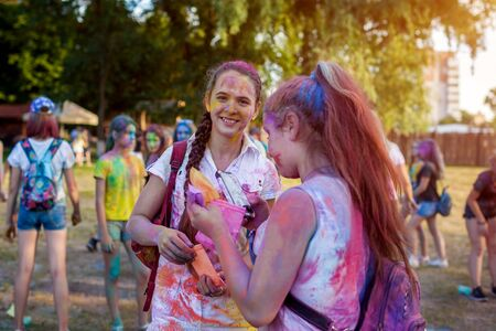 Myrhorod, Ukraine - June 16, 2019: Young friends throwing paints on indian Holi festival of colors