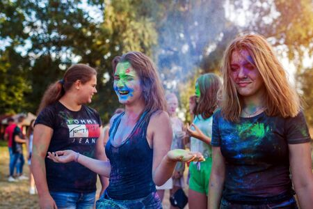 Myrhorod, Ukraine - June 16, 2019: Group of a young friends throwing paints on indian Holi festival of colors Publikacyjne