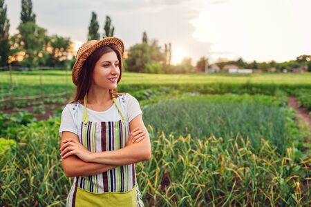 Young woman farmer looking at vegetables on kitchen-garden in countryside. Agriculture and farming concept. Organic farm