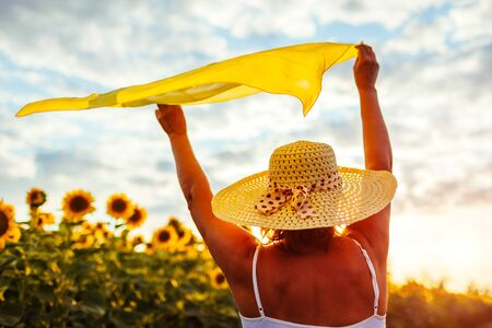 Senior woman walking in blooming sunflower field raising hands with scarf and having fun. Summer vacation Banque d'images