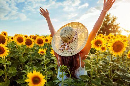Glückliche junge Frau, die in blühendes Sonnenblumenfeld geht, Hände hebt und Spaß hat. Sommerurlaub.