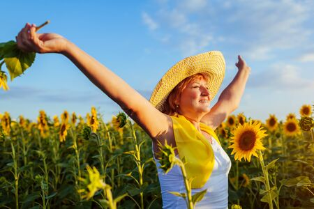 Happy senior woman walking in blooming sunflower field feeling free and admiring view. Summer vacation.
