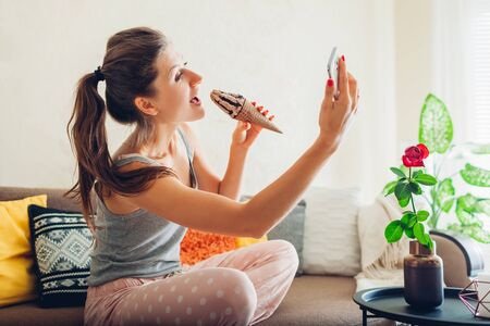 Young woman eating chocolate ice-cream in cone sitting on couch at home and taking selfie using smartphone.