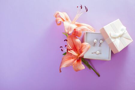 Set of pearl jewellery in the gift box with flowers. Earrings and ring with lily on purple background