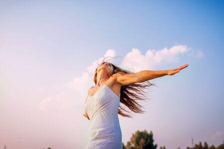 Jonge vrouw die zich vrij en gelukkig voelt en haar armen opheft en buiten ronddraait bij zonsondergang