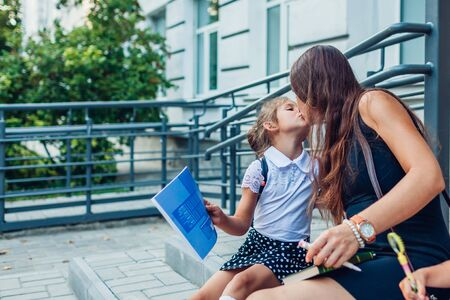 Happy mother kissing daughter after classes. Children doing homework outdoors primary school sitting on stairs. Reklamní fotografie - 130542114