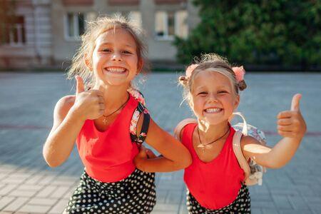 Happy sisters girls wearing backpacks and showing thumbs up. Kids pupils having fun outdoors school building. Education. Back to school Standard-Bild