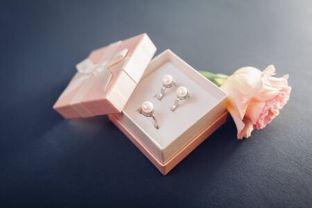 Set of pearl jewellery in gift box with flowers on grey background. Silver earrings and ring with pearls as a present for holiday. Accessories and jewelry.