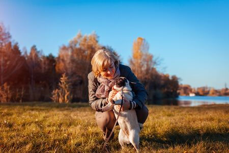 Walking pug dog in autumn park by river. Happy woman hugging pet and having fun with best friend outdoors. Archivio Fotografico - 130645352