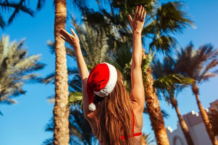 New Year and Christmas celebration. Woman in Santas hat and bikini relaxing in swimming pool. Tropical holiday vacation