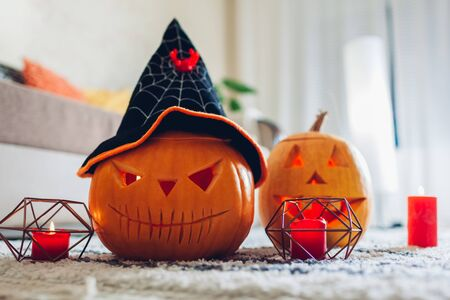 Halloween jack-o-lantern pumpkins. Home decorated with traditional Halloween symbols. Spooky pumpkins with candles put on living room carpet