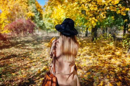 Autumn vibes. Young woman walking in autumn forest among falling leaves. Stylish girl wearing hat and coat Stok Fotoğraf
