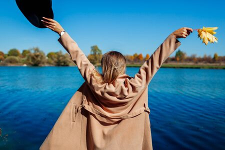 Autumn vibes. Young woman relaxing by river and having fun. Girl raising arms welcoming fall. Nature detox