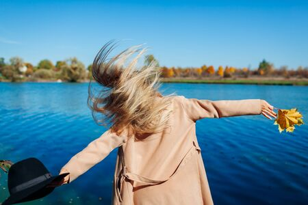 Autumn mood. Young woman jumping by river and having fun. Girl raising arms welcoming fall