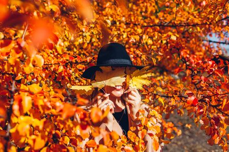 Autumn fun. Young woman walking in autumn forest covering eyes with leaves. Girl having fun Banco de Imagens