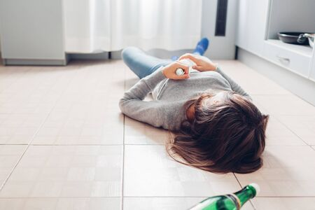 Female alcohol addiction. Young woman sleeping on kitchen floor after party holding bottle. Alcoholism 版權商用圖片