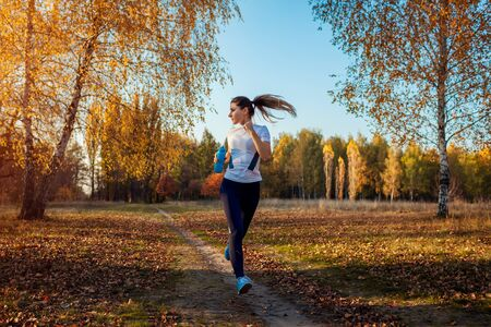 Runner training in autumn park. Woman running with water bottle at sunset. Active lifestyle. Workout Stock fotó