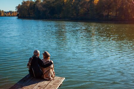 Senior family couple relaxing by autumn lake. Happy man and woman enjoying natural landscape and hugging sitting on pier