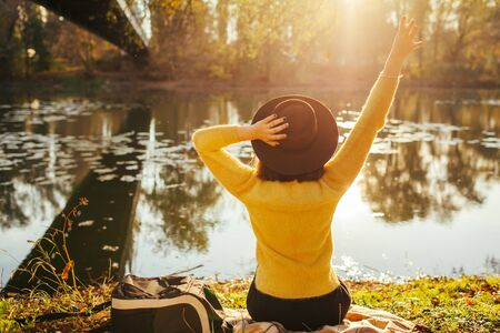 Traveler relaxing by autumn river at sunset. Young woman tourist sitting on bank raising hands and holding hat. Autumn activities