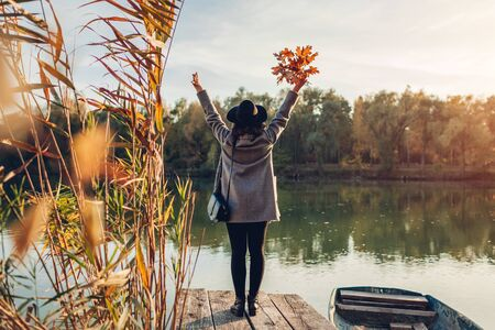 Happy woman walking on lake pier by boat raising hands and admiring autumn landscape. Fall season activities Imagens