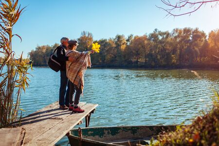 Autumn season. Senior family couple walking by autumn lake. Happy man and woman enjoying natural landscape and hugging on pier