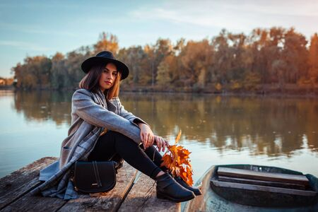 Woman sitting on lake pier by boat admiring autumn landscape and relaxing. Fall season activities