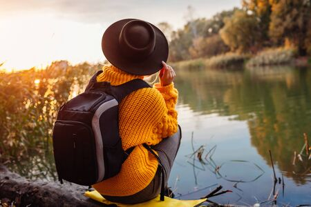 Traveler with backpack relaxing by autumn river at sunset. Young woman admires nature. Active lifestyle