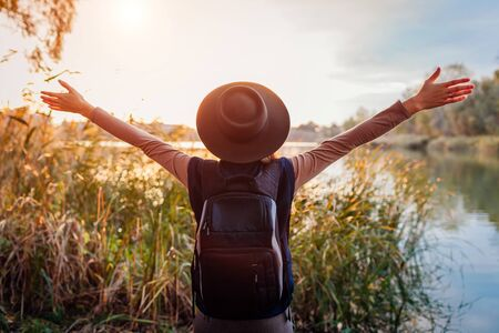 Traveler with backpack relaxing by autumn river at sunset. Young woman raised arms feeling free and happy. Active lifestyle Stockfoto