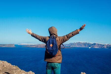 Man traveler raised arms feeling free and happy on Santorini island in autumn. Tourist admiring Caldera view, sea and mountain landscape
