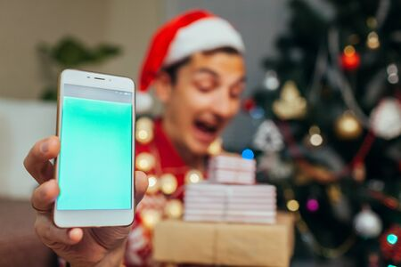 Christmas gifts delivery. Man ordered New year presents using smartphone. Happy guy holding gift boxes and phone with green screen Stockfoto