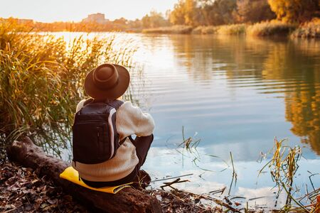 Tourist with backpack sitting on river bank at sunset. Senior lonely woman relaxing and admiring autumn nature. Travelling concept