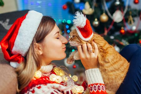 Christmas celebration with cat. Woman playing and kissing pet in Santas hat by New year tree at home. Family having fun